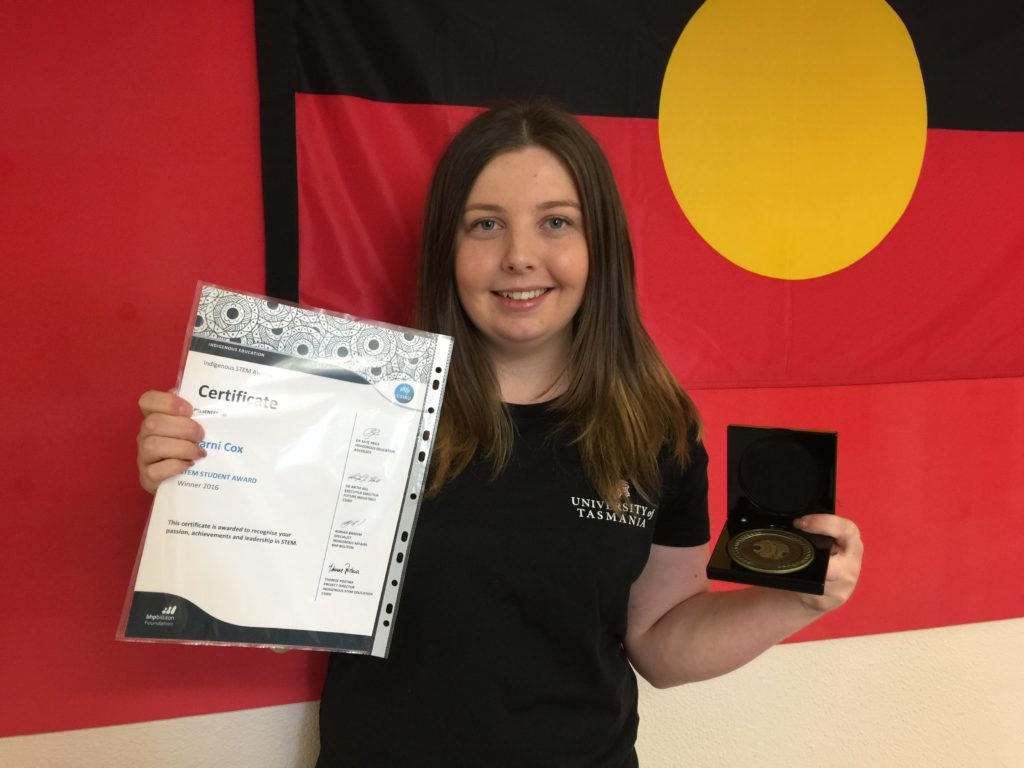 Sharni Cox standing in front of the Australian Aboriginal Flag with the medal and certificate for the 2016 Student STEM Award.