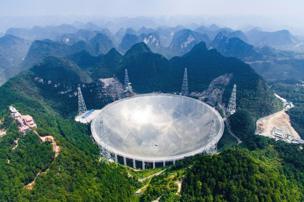 Large white telescope dish set in the ground surrounded by green mountains.