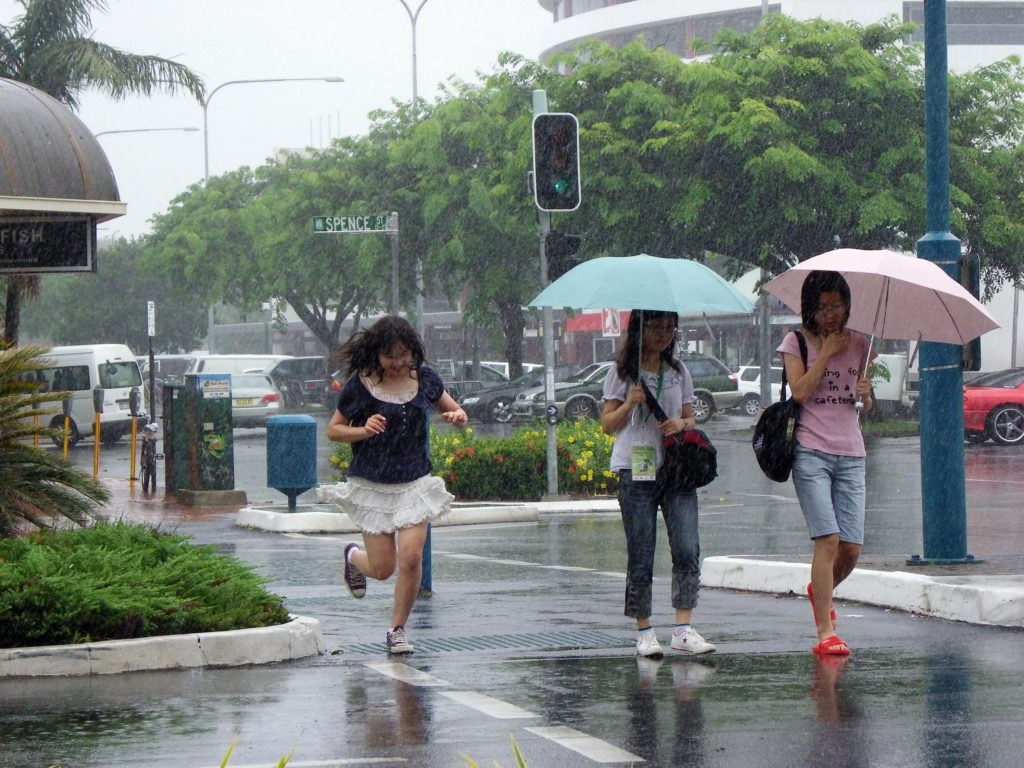 people crossing the road as it rains