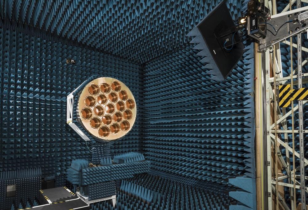 Large gold disc with 19 holes on its face set up on a stand in the middle of a room covered with blue foam cones.