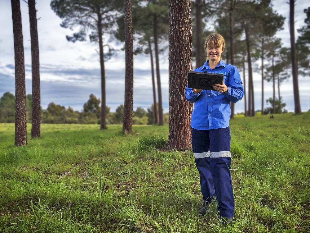 Female in blue overalls staining in a field holding a tablet device