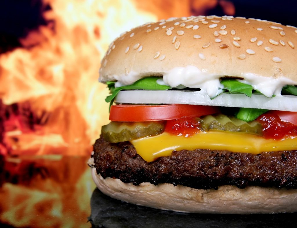 Stock image of a burger in front of flames