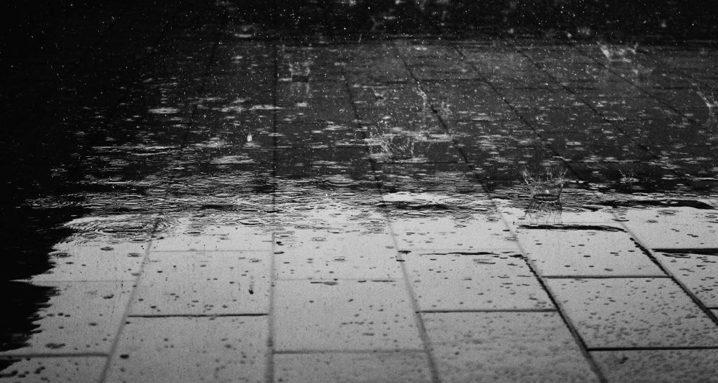 a paved surface with rain falling