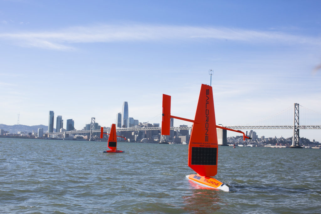 Two Saildrones seen sailing in the water. Buildings are visible in the far distance.