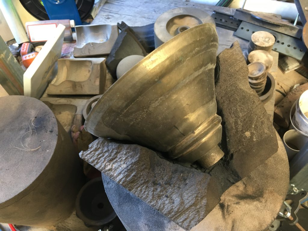large brass bell sits on messy work bench surrounded by cloths and tools