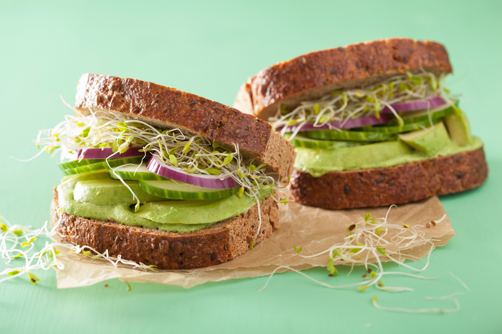 avocado and salad sandwich on a piece of brown paper