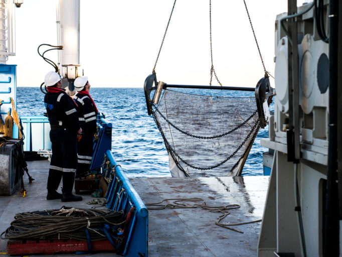 Two people aboard a ship watching a large net being hauled back onto the deck.