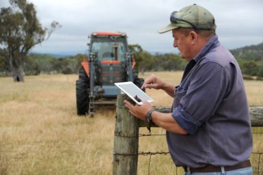 a farmer on an ipad with a tractor in the background