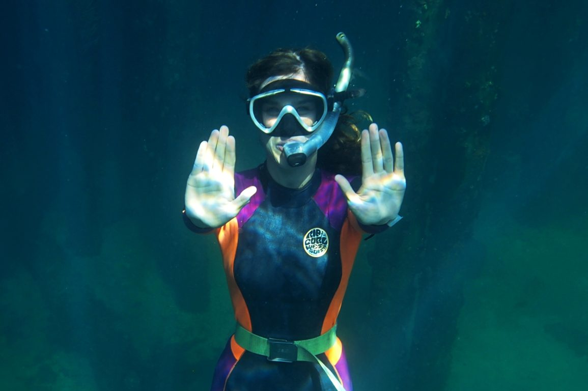 Anna cresswell underwater in scuba gear pushing an imaginary button