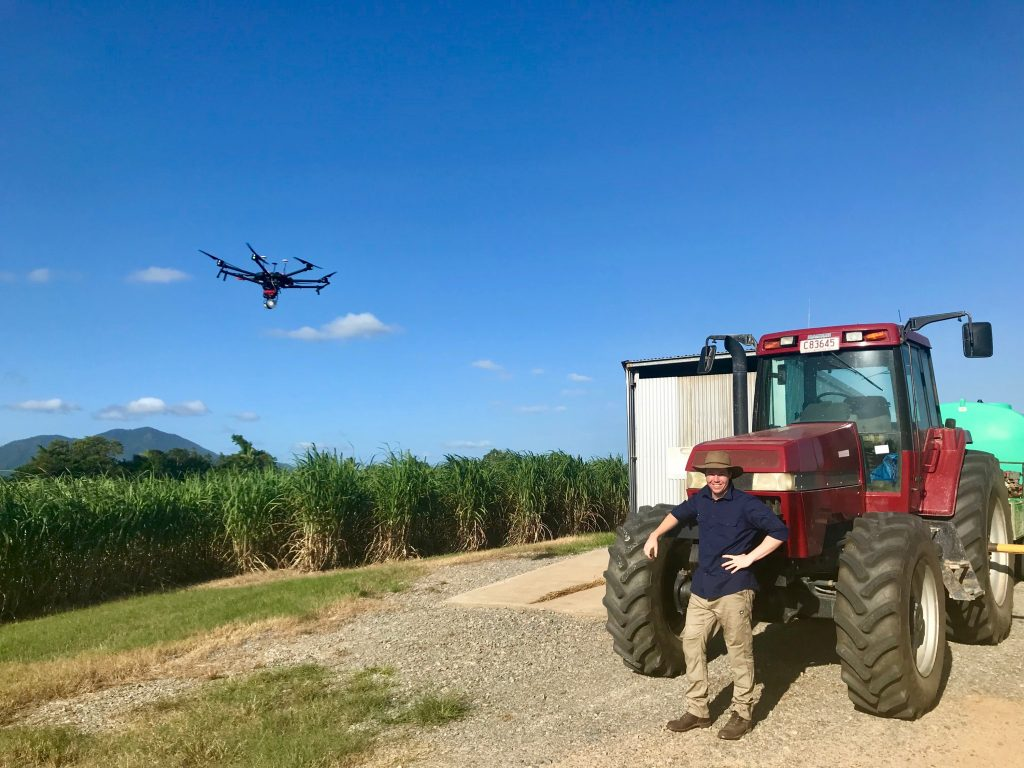 A man and a tractor beside a sugar cane field with a drone