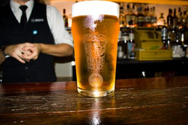a pint glass of beer on a bar