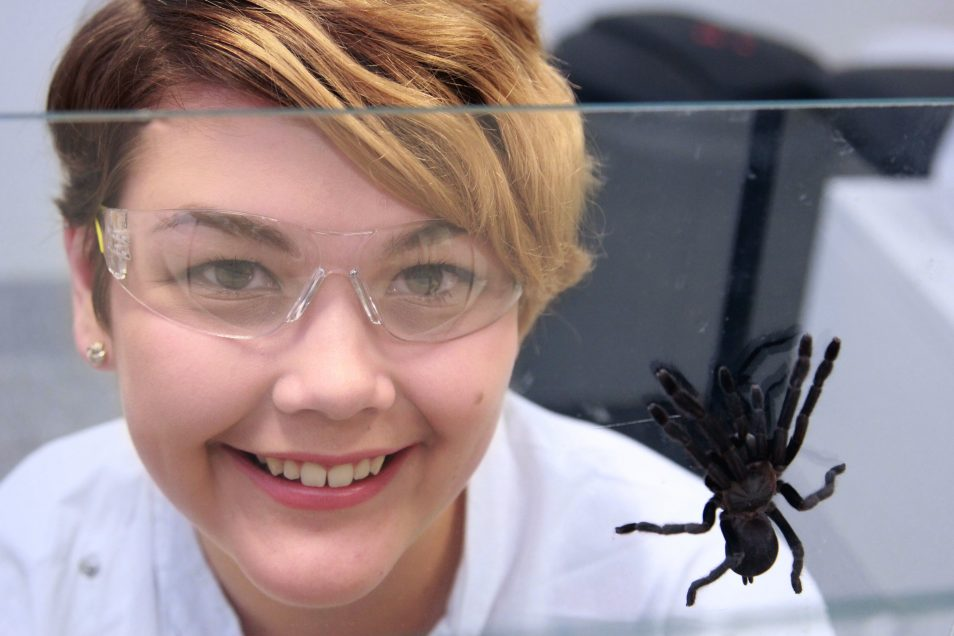 Samantha standing next to a spider in her lab