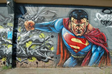 street art mural of superman with glowing eyes