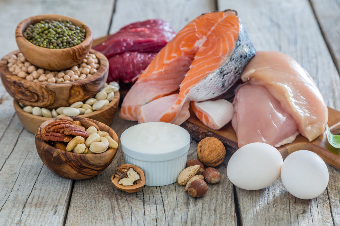 Healthy sources of protein including eggs, fish, nuts and chicken are piled in bowls and a wooden board.