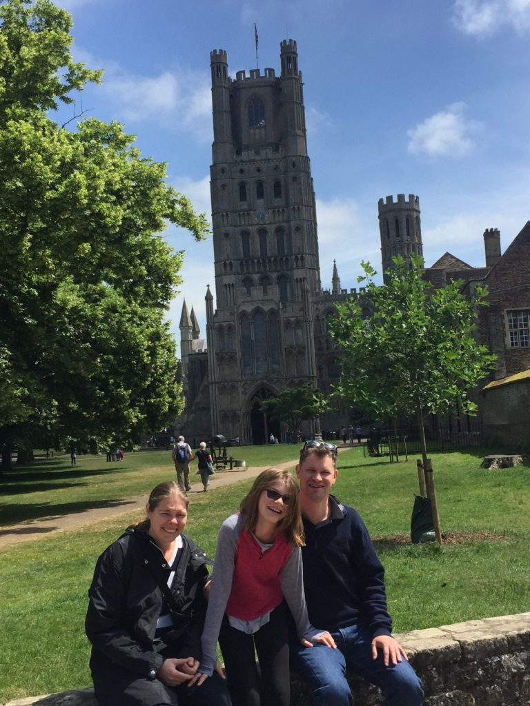 Family of mum, dad and daughter sit on wall surrounding park in front of old cathedral on sunny day