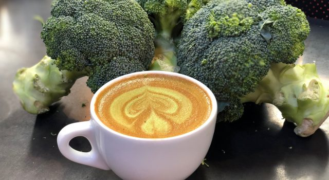 A broccoli latte surrounded by bunches of raw broccoli