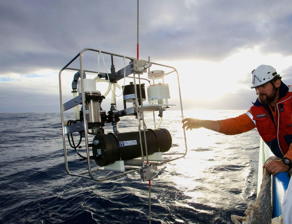 With flat seas, Mark Lewis works with an In situ pump alongside Investigator in the Southern Ocean