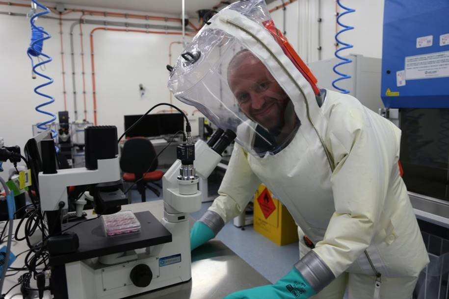 A man wears a protective suit and helmet in a lab, standing in front of a microscope