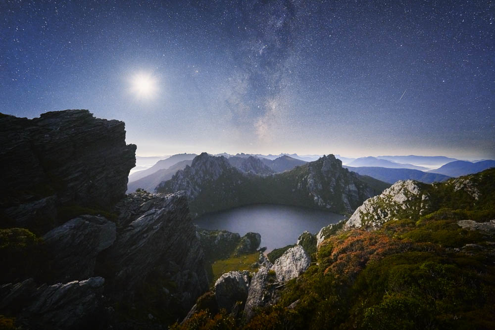 The crescent moon and milky way shine over the misty Lake Oberon in Tasmania