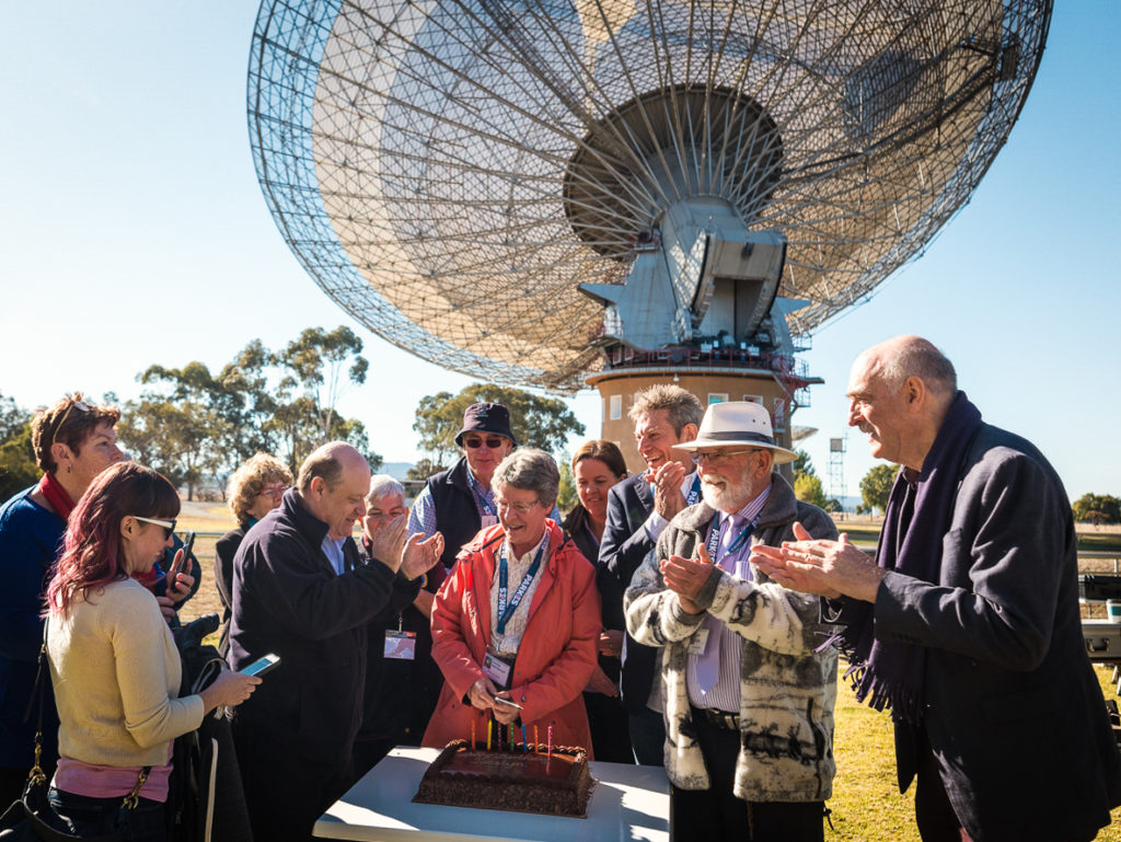 Group of people stanine around birthday cake on table in front of radio telescope