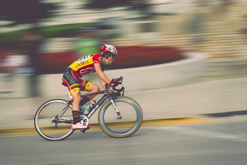 A professional cyclist riding up a hill at speed