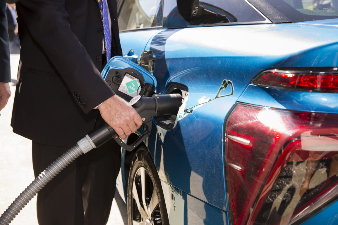 Man filling a hydrogen car with fuel
