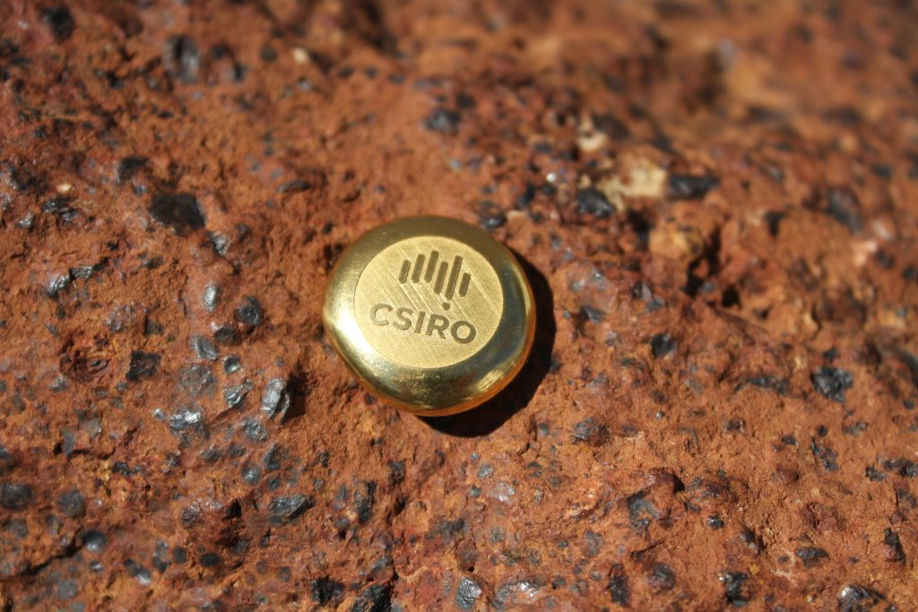 round gold ingot featuring CSIRO logo resting on a slice of rock ore