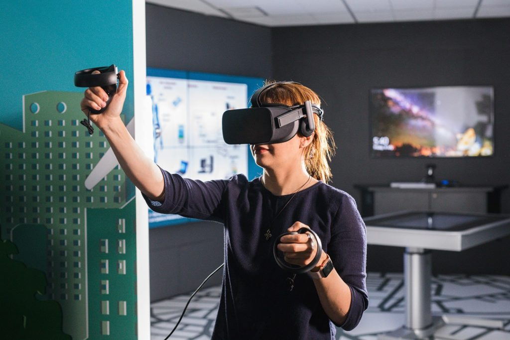 young woman in high tech lab wearing virtual reality device over her eyes