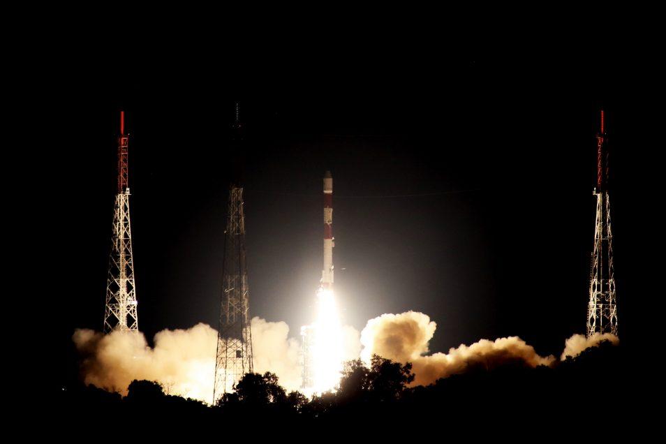 White rocket blasting off at night with orange flames below.