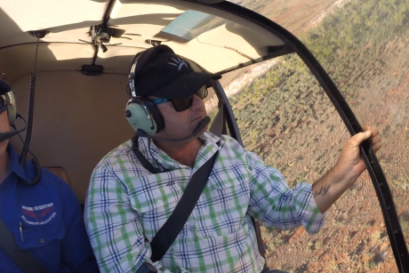 Contract ariel muster, Jonathon Campbell in a helicopter over the pilbara