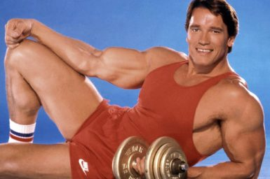 A 1980s photo of Arnold Schwarzenegger smiling at the camera holding weights