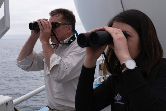 Dr Eric Woehler and Cassie Layton looking through binoculars