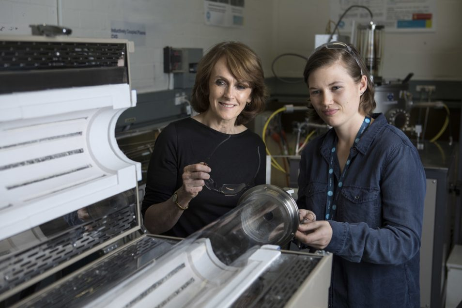 Chief scientist Cathy Foley smiling, standing next to a female student in a dark blue shirt, both looking at GraphAir lab technology