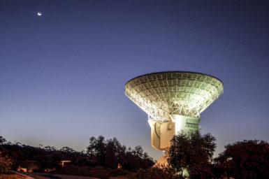 White dish-shaped antenna with the night sky behind it.
