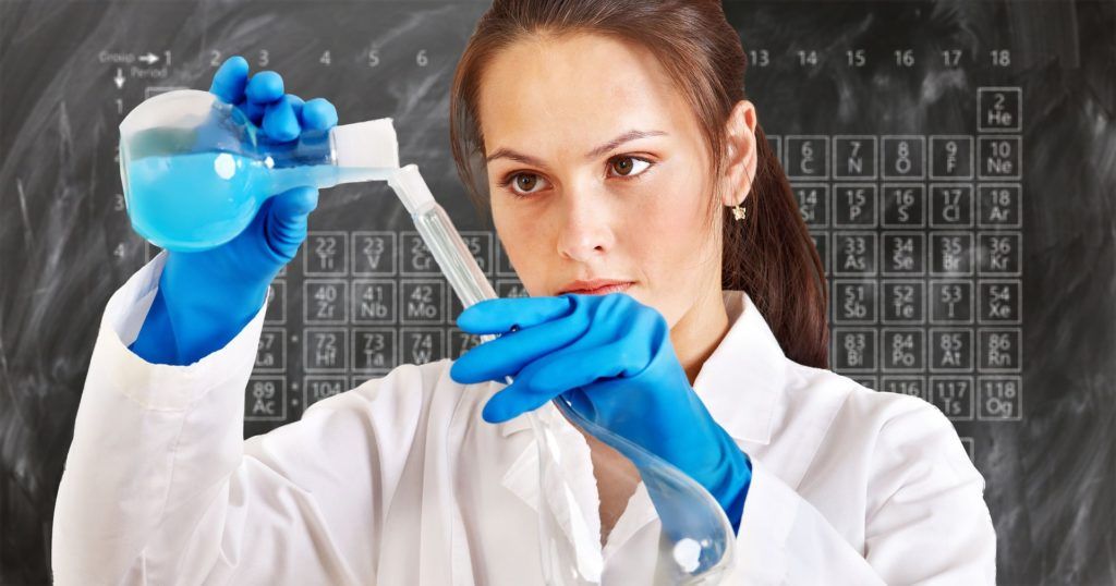 female chemist pouring chemicals with a blackboard showing the periodic table in the background