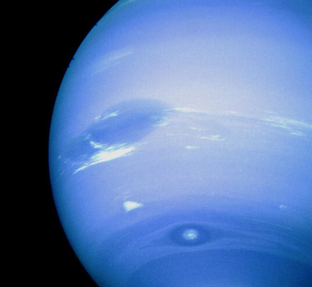 Neptune's Great Dark Spot, accompanied by white high-altitude clouds