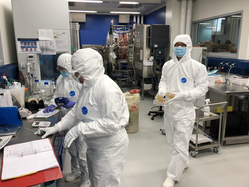 Three scientists wearing white safety suits, in a lab. One is pointing at a folder on a table.