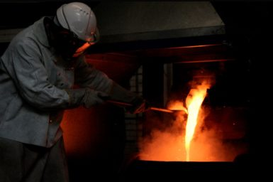 Person smelting metal in a kiln