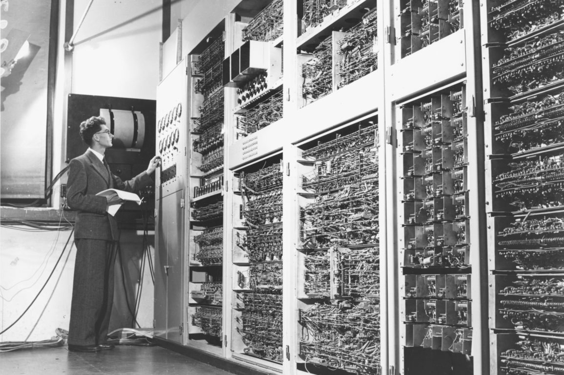 An old black and white image of scientist working with Australia's first computer, CSIRAC.