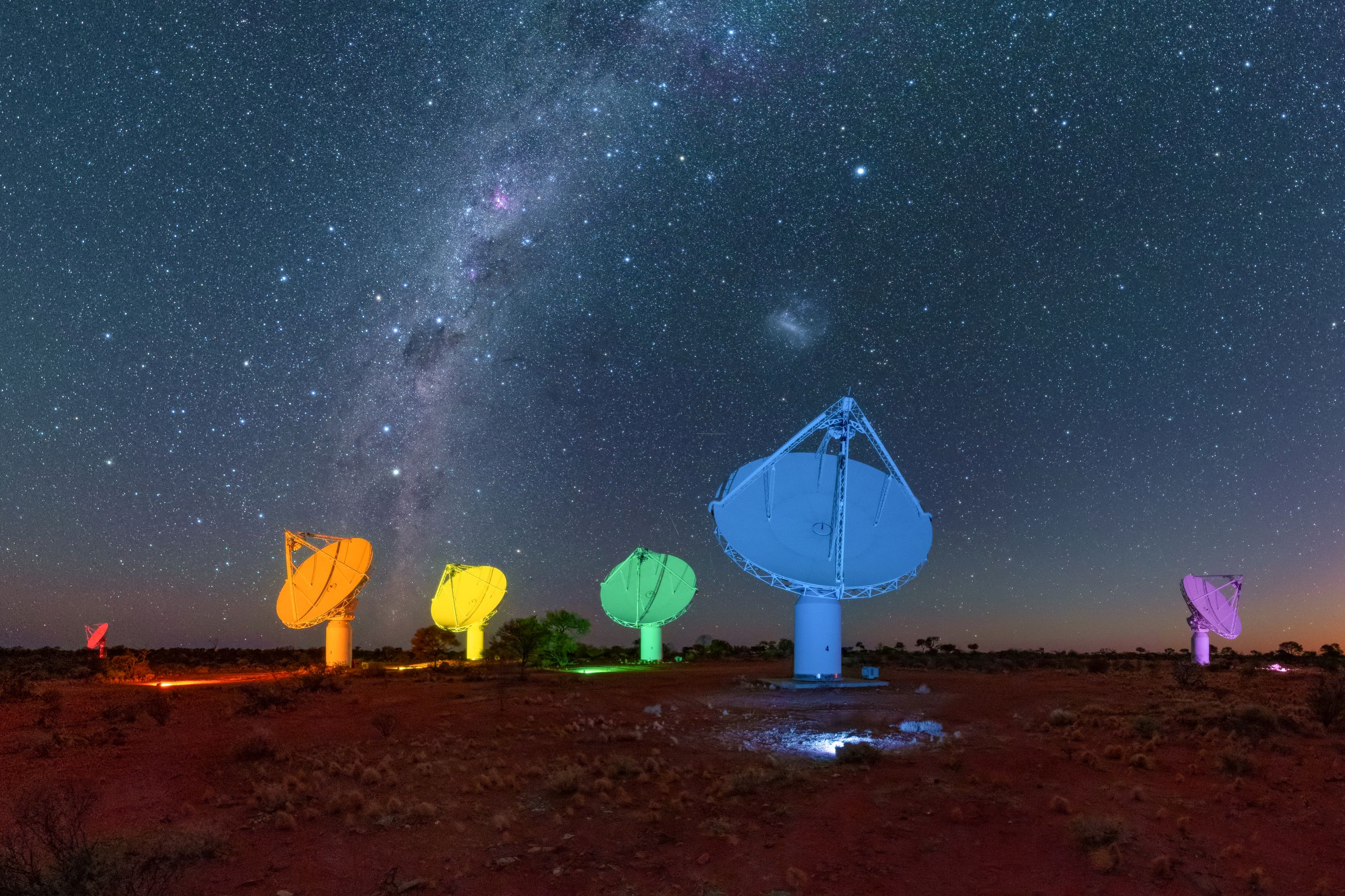 A photo of five telescopes lit in the colours of the rainbow, for the Sydney Gay and Lesbian Mardi Gras parade.