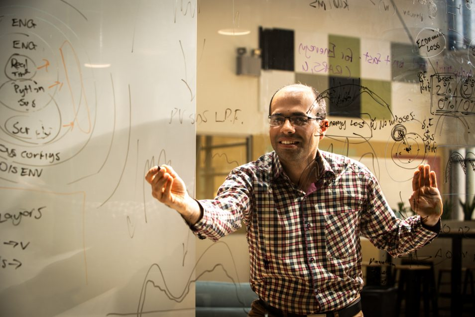 Dr Nariman Mahdavi Mazdeh works out some equations on a clear screen.