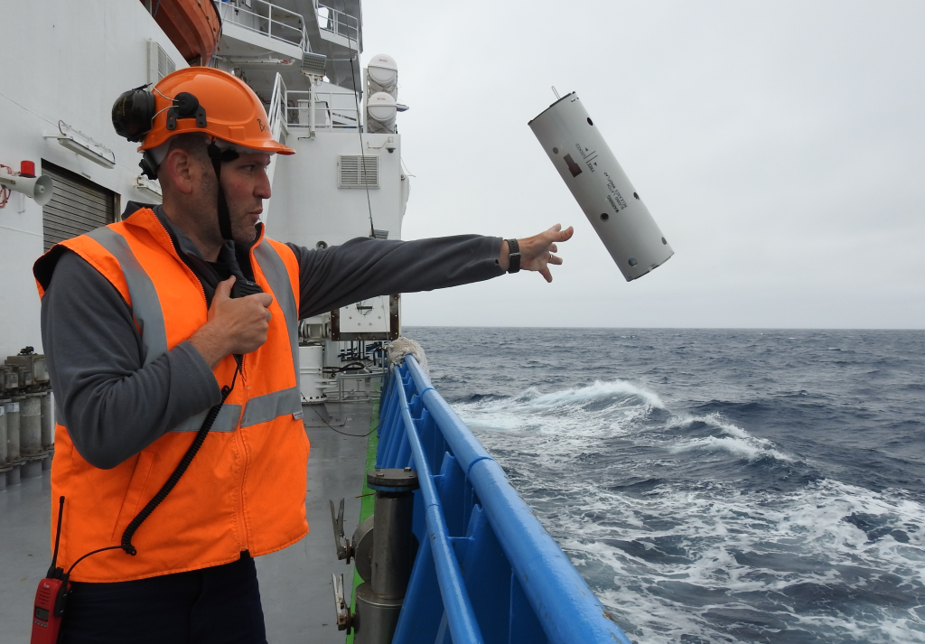 researcher dropping sonobuoy device over the side of the ship