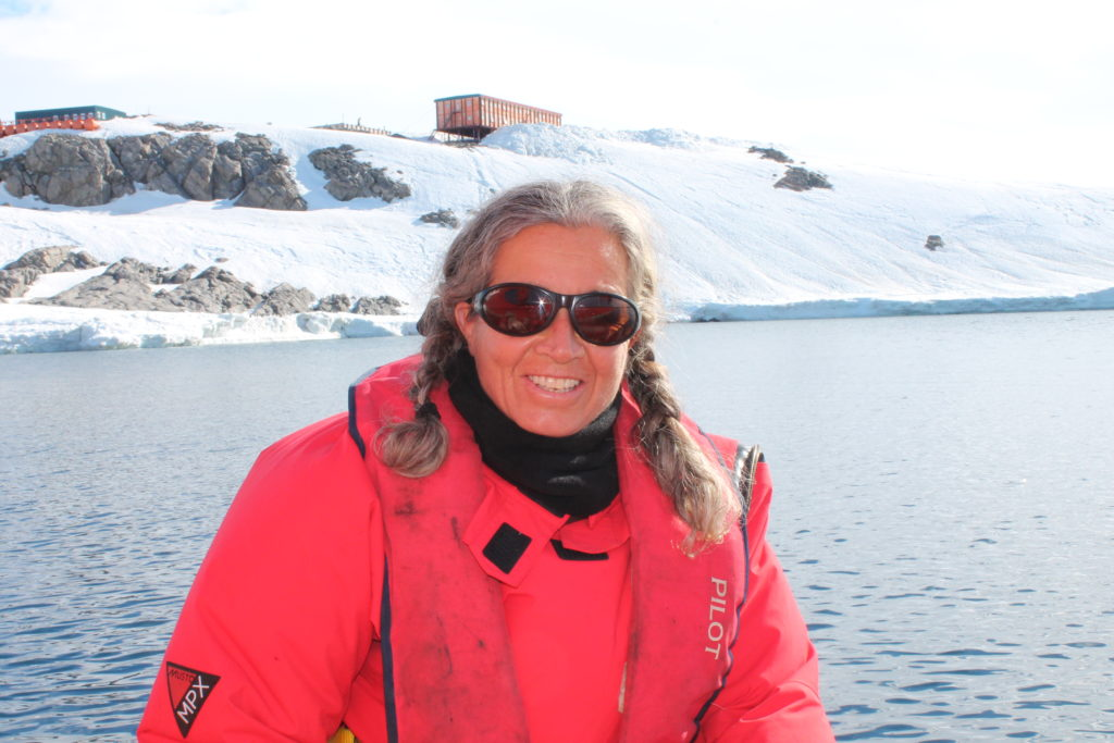 Madeleine Habib has been a ship's captain on the Investigator. Here she stands in front of an Antarctic base.