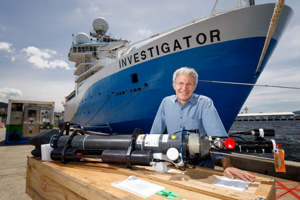 Dr Steve Rintoul standing behind a long, black, cylindrical metal object, which is an Argo float. In the background towers a large blue and white ship, the RV Investigator.