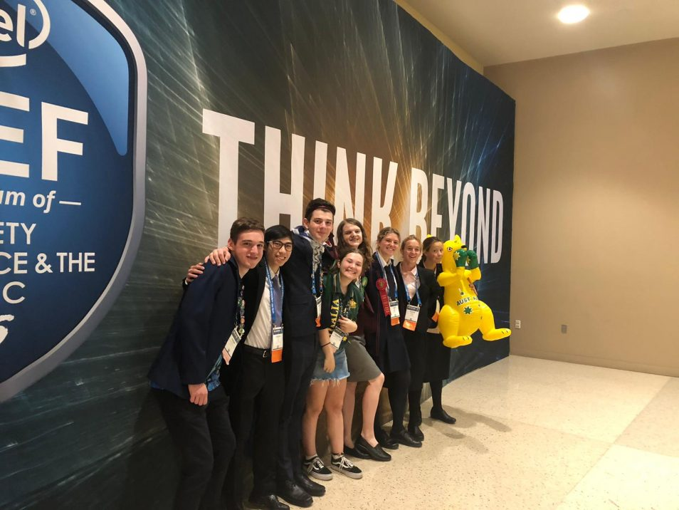Group of students standing in front of sign that says Think Beyond.