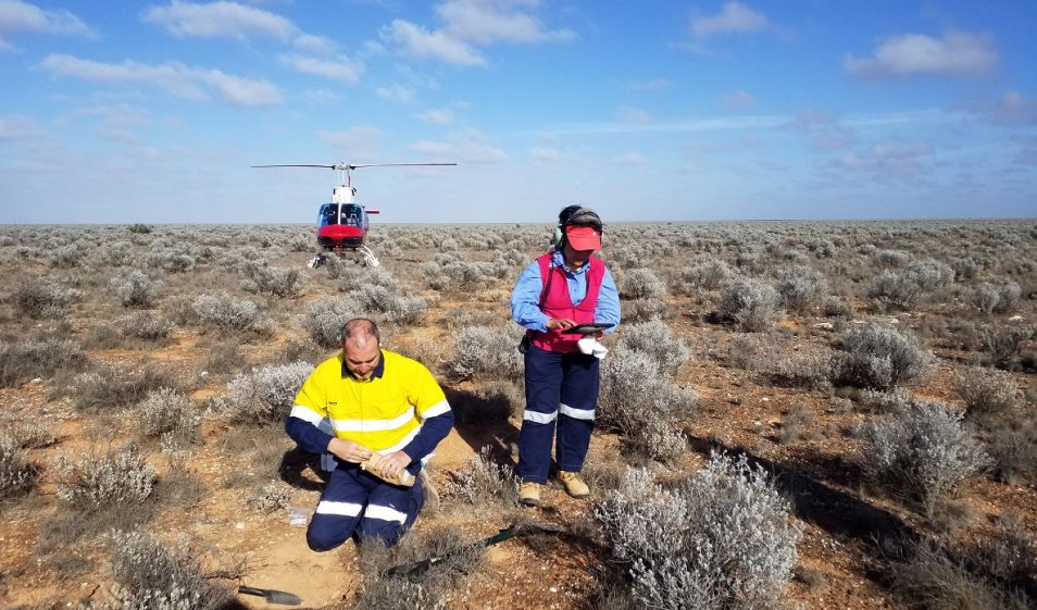 Male and female scientists taking soil samples from a remote landscape showing a helicopter in the background