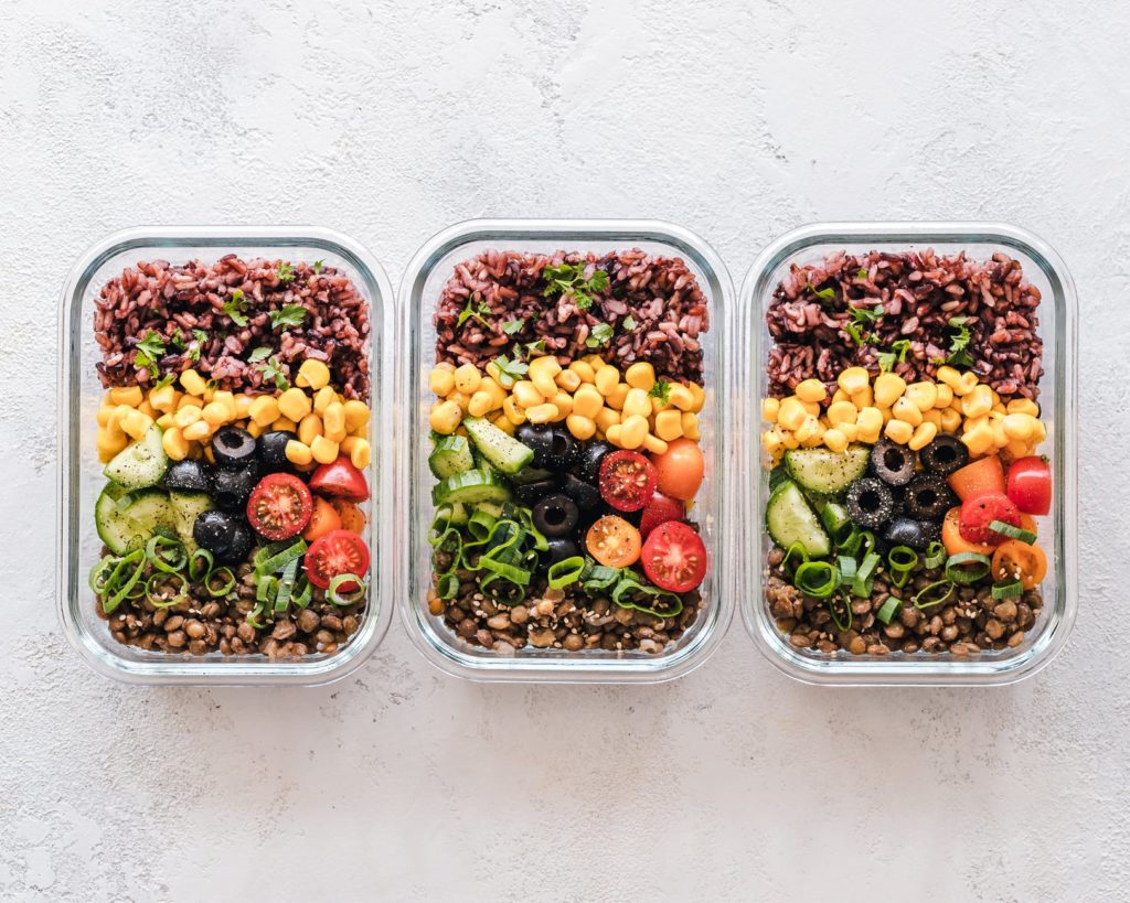 three containers of salad and brown ricethat have been prepared for the week