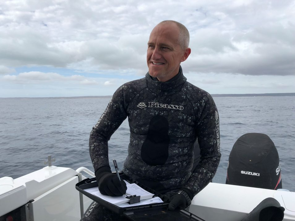 Dr Richard Pillans wears a wetsuit while sitting on a boat