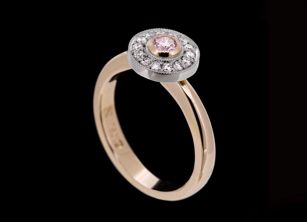 Gold ring featuring a circle of white diamonds around a pink central diamond