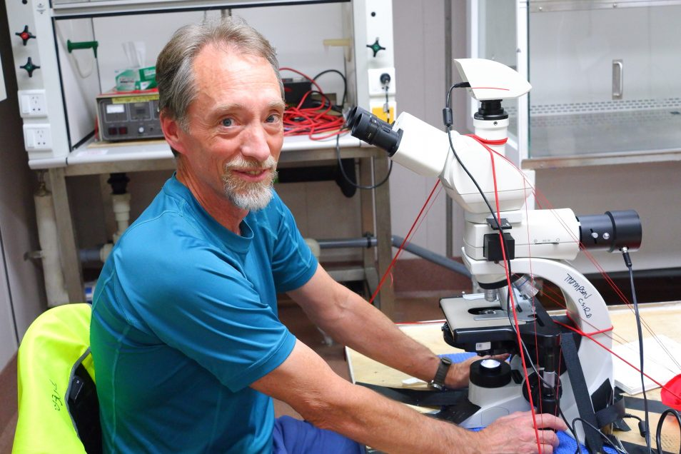 CSIRO researcher Dr Peter Thompson sitting at a microscope, looking to camera